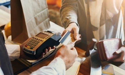 homem passando seu cartão de crédito em uma loja
