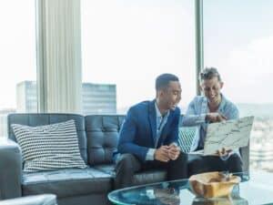 dois homens conversando sobre as vantagens de investir em ações