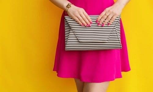 mulher de vestido rosa segurando uma clutche
