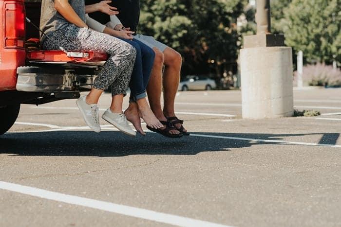 3 pessoas sentadas na parte de trás de uma caminhonete