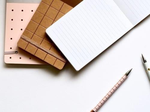 Cadernetas e lapiseiras sobre a mesa