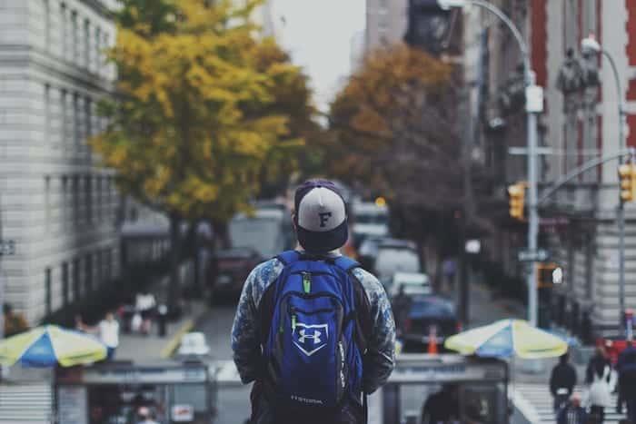 Rapaz com mochila nas costas, parado e olhando a rua