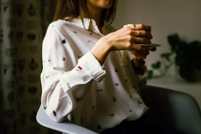 Mulher sentada em uma cadeira, tomando chá