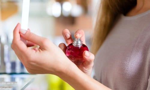 mulher borrifando perfume em seu pulso