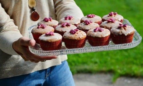 pessoa segurando uma bandeja de cupcakes