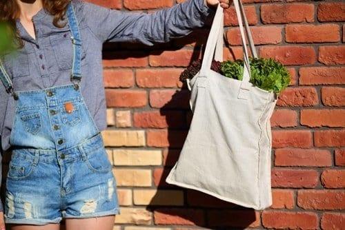 mulher segurando uma ecobag com verduras dentro