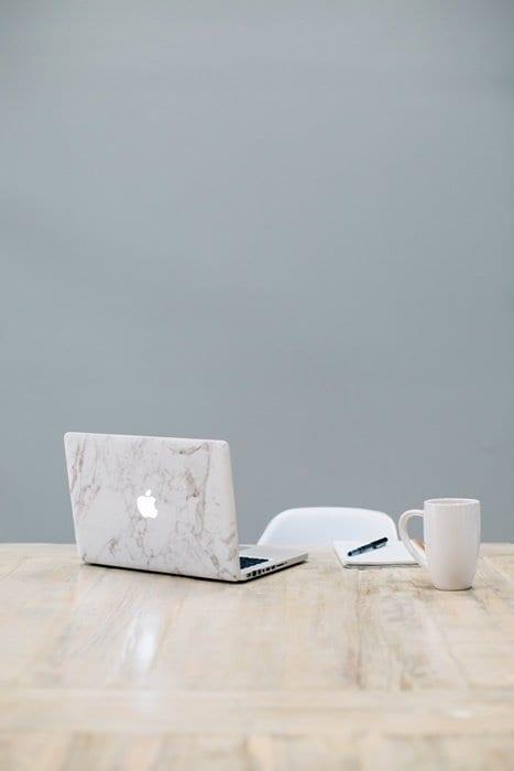 Notebook, caneca e caneta sobre a mesa