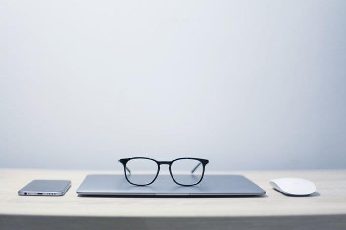 Notebook, mouse, óculos e celular sobre uma mesa