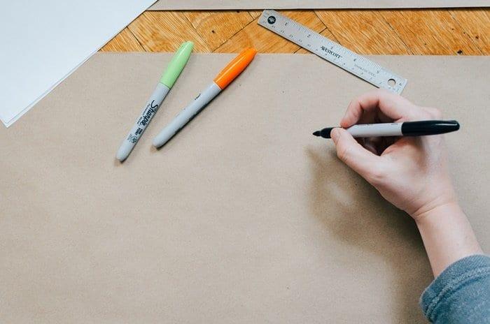 Pessoa segurando caneta para escrever em um cartaz