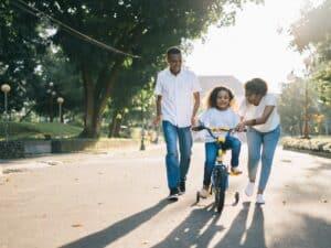Imagem de uma família feliz em um parque, com uma criança aprendendo a andar de bicicleta, representando nosso conteúdo sobre orçamento familiar