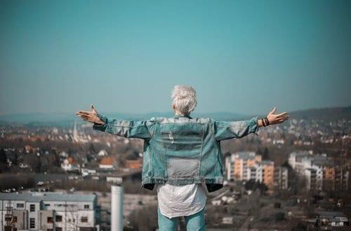homem de braços abertos olhando para a cidade