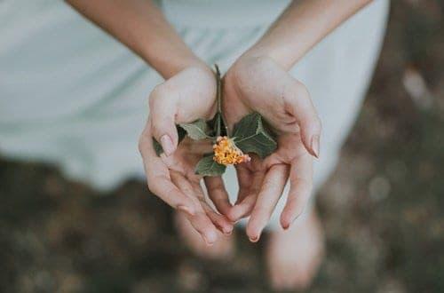 Mulher segurando flores - Cuidados Pessoais