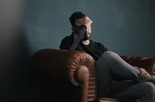 homem com a mão na cabeça sentado em um sofá