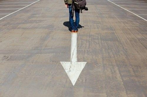 Pessoa em pé sobre seta no chão