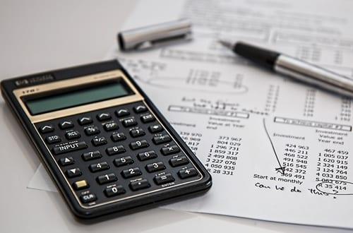 uma calculadora, caneta e um papel escrito em cima de uma mesa