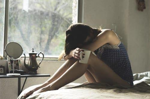 mulher triste de cabeça baixa enquanto abraça os próprios joelhos
