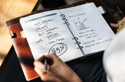pessoa escrevendo tabelas e porcentagens em um caderno
