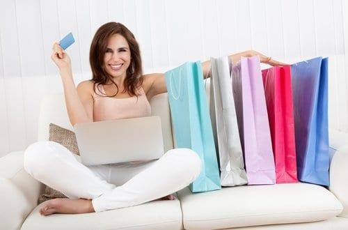 mulher com um notebook no colo, segurando um cartão de crédito e com várias sacolas de compras ao lado