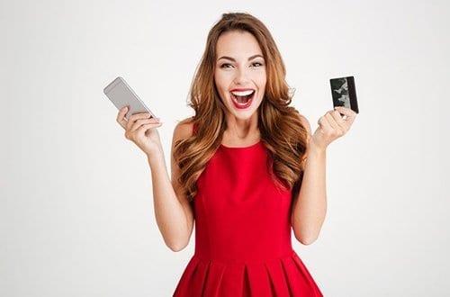 mulher segurando um celular em uma mão e na outra um cartão de crédito sem anuidade