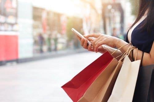 mulher com várias sacolas mexendo no celular