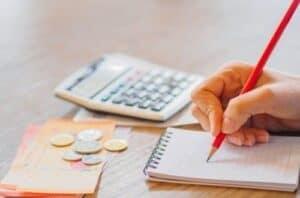 Pessoa anotando os débitos para começar a quitar as dívidas e tentar limpar seu nome