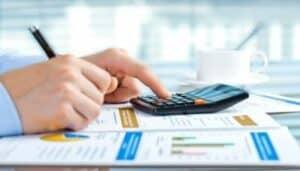 Mão segurando caneta e calculadora para representar o tema controle de orçamento