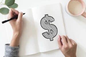 mulher desenhando o símbolo cifrão em um caderno em branco simbolizando erros financeiros das pessoas pobres