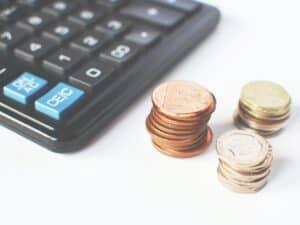 Imagem de uma calculadora e moedas em cima de uma mesa para representar o conteúdo sobre juros compostos