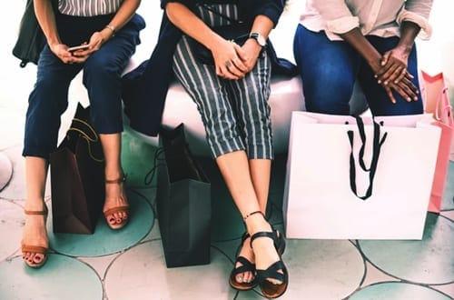 três mulheres sentadas com várias sacolas de compras
