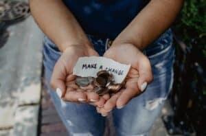 Pessoa com moedas na mão pensando sobre Como sair do vermelho