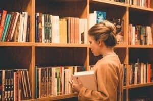mulher segurando um livro em frente a uma estante enorme de livros