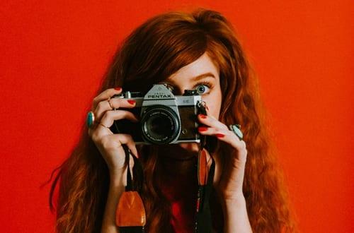 mulher segurando uma câmera fotográfica vintage