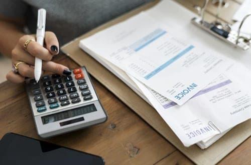mulher usando a calculadora ao lado de várias contas