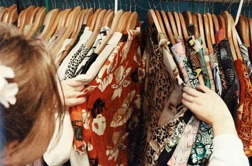 mulher olhando roupas em um brechó
