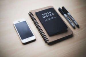 Foto de smartphone, caderno e canetas sobre a mesa simbolizando o tema aplicativo de metas