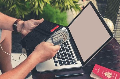 pessoa com uma carteira na mão enquanto faz um doc ou ted no notebook