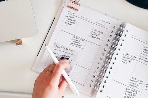 Pessoa escrevendo suas metas para 2020 em um caderno