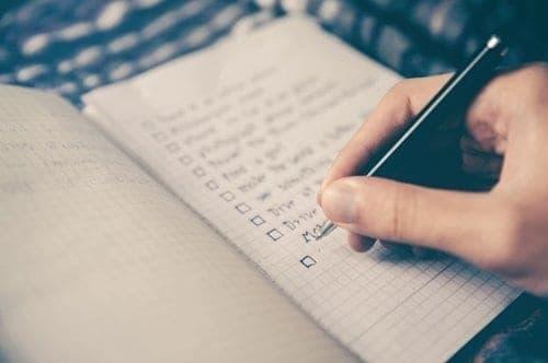 Pessoa fazendo no caderno suas listas de compras