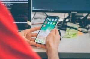 pessoa mexendo no celular simbolizando economizar nas contas de celular