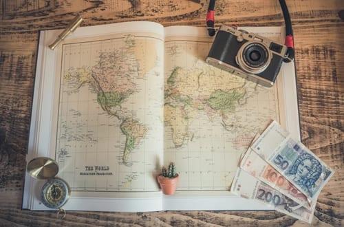 um mapa mundi com uma câmera e dinheiro ao lado