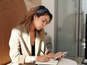 Imagem de uma mulher em sua mesa, escrevendo em um caderno e usando o celular. Ela poderia estar entendendo, por exemplo, o que é o cheque legal, motivo deste conteúdo.