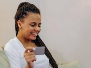 Imagem de uma mulher usando o cartão de crédito e sorrindo. Usamos a foto para ilustrar o post que discute o que acontece quando alguém pagar metade da fatura do cartão