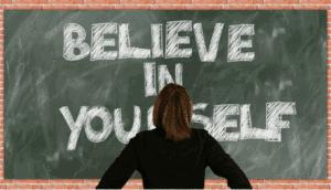 Mulher vendo um quadro onde está escrita uma frase sobre autoestima