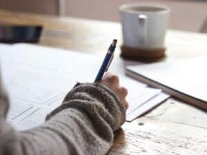 Imagem de uma pessoa fazendo anotações com uma lapiseira, representando o conteúdo sobre educação financeira