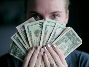 Imagem de uma mulher com várias notas de dólares na mão, representando nosso conteúdo sobre como ficar rico