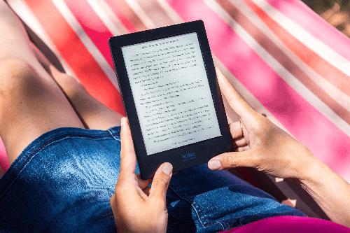 Pessoa deitada em uma rede lendo um e-book para simbolizar o tema Aplicativo de livros