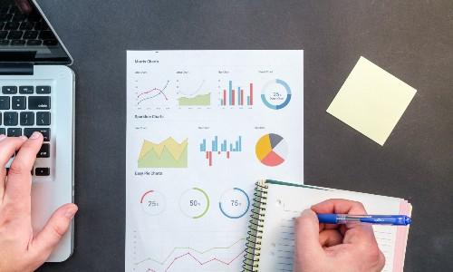 Imagem de uma pessoa em uma mesa com computador e vários gráficos, quem aprende como trabalhar pela internet respondendo pesquisas oferece informações valiosas para as empresas