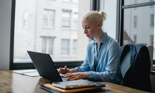 Imagem de uma mulher trabalhando no computador, ela entendeu como trabalhar pela internet sendo assistente virtual