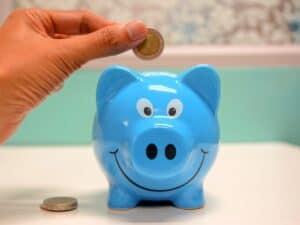 Imagem de uma pessoa guardando dinheiro no cofrinho para melhorar as despesas mensais