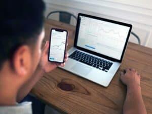 homem observando home broker em celular e computador